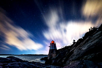 Castle Hill Lighthouse in Newport, Rhode Island and cliffs along the ocean with a long exposure sky featuring clouds and stars