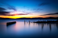 Long Exposure of a marina in spring time with smooth water, clouds and mountains at sunset